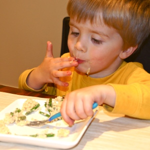 Child eating quinoa & asparagus
